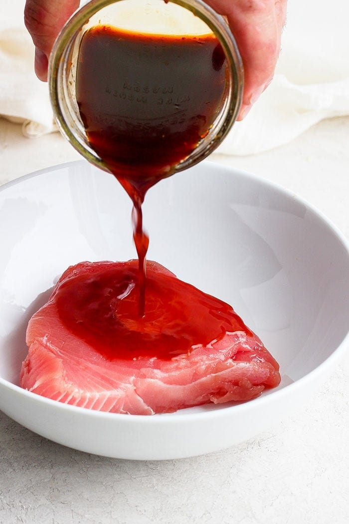 pouring marinade onto an ahi tuna steak