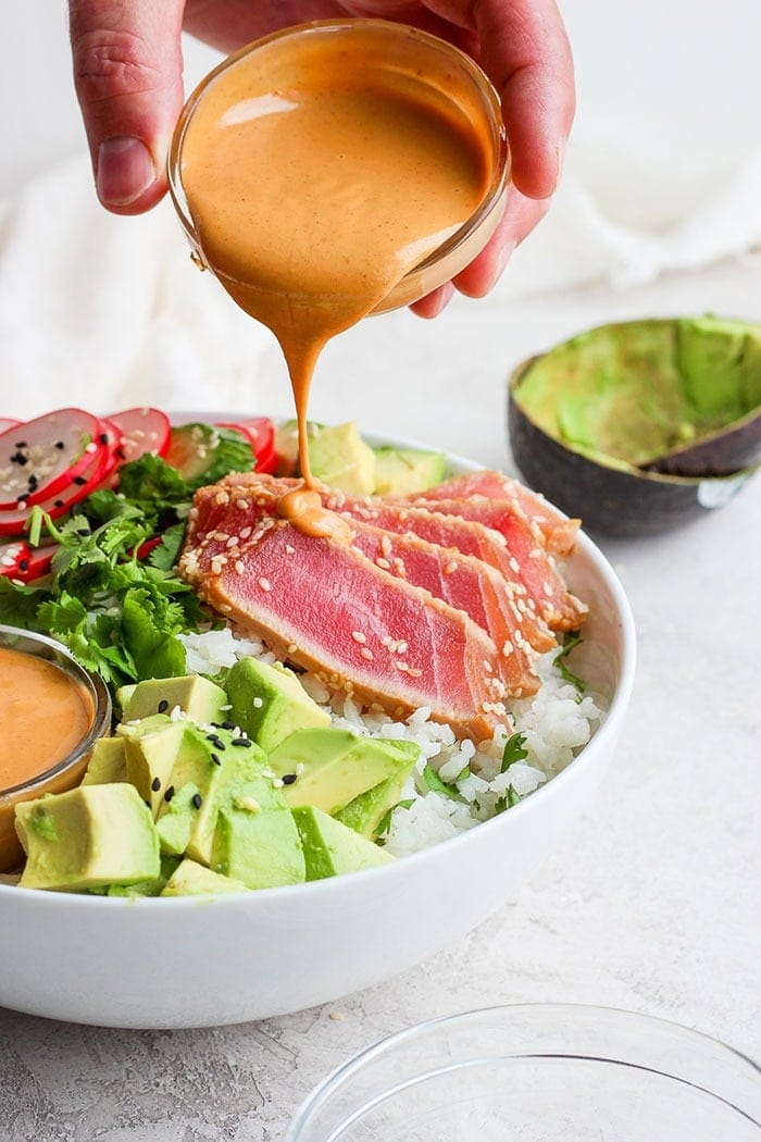Drizzling almond dressing onto the poke bowl