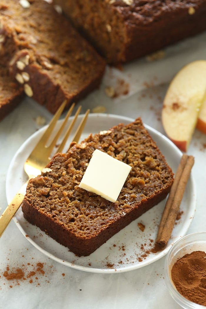 slice of cinnamon apple bread on a plate with a pad of butter