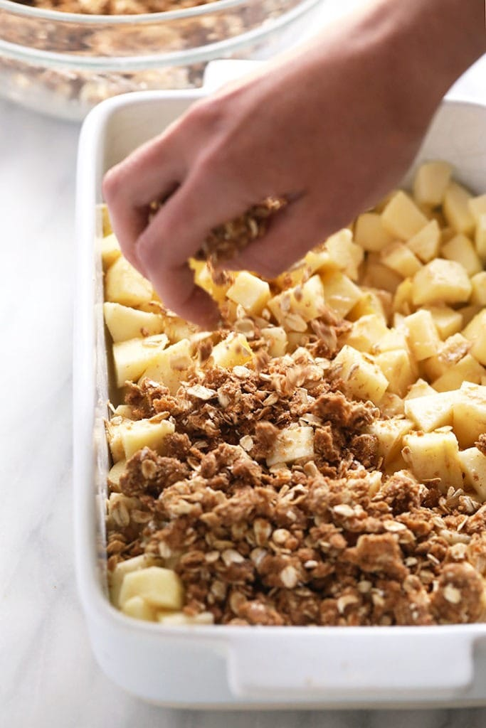 sprinkling crumble topping on apples