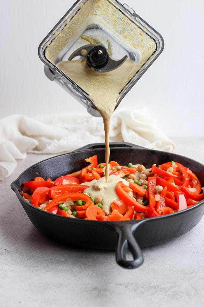 creamy cashew curry sauce being poured over sautéed veggies