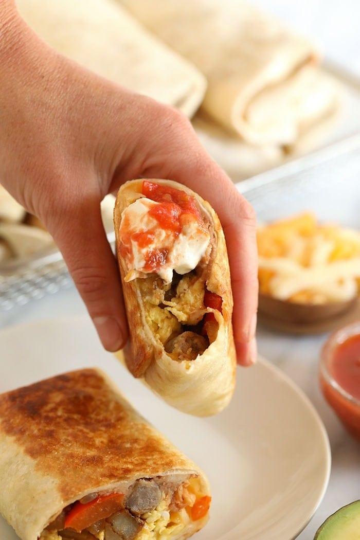 A hand holding fajita breakfast burritos
