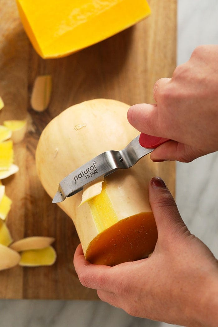 butternut squash being peeled with a vegetable peeler