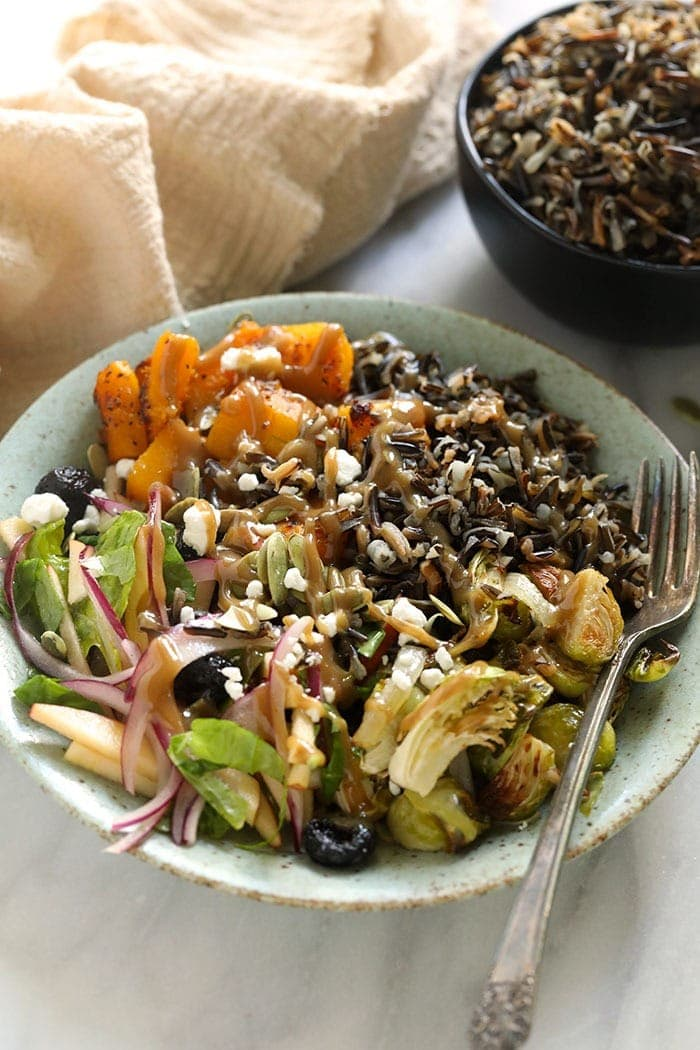 vegetarian harvest grain bowl with tahini dressing in a bowl