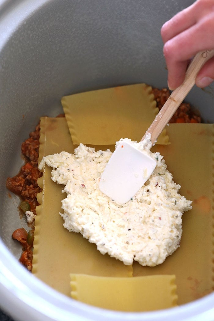 Spreading cheese mixture on lasagna noodles