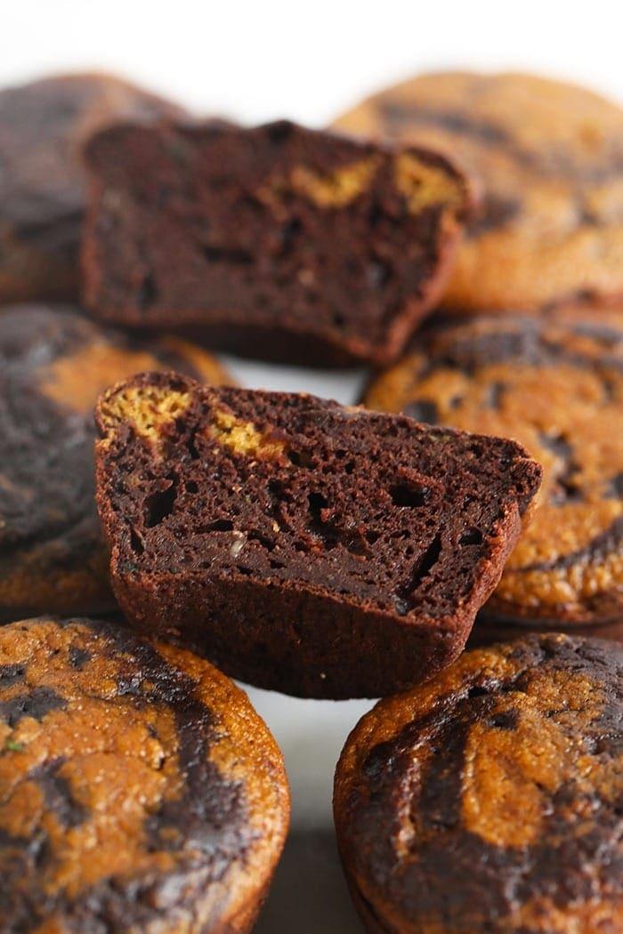chocolate pumpkin zucchini muffins cut in half to show the swirl
