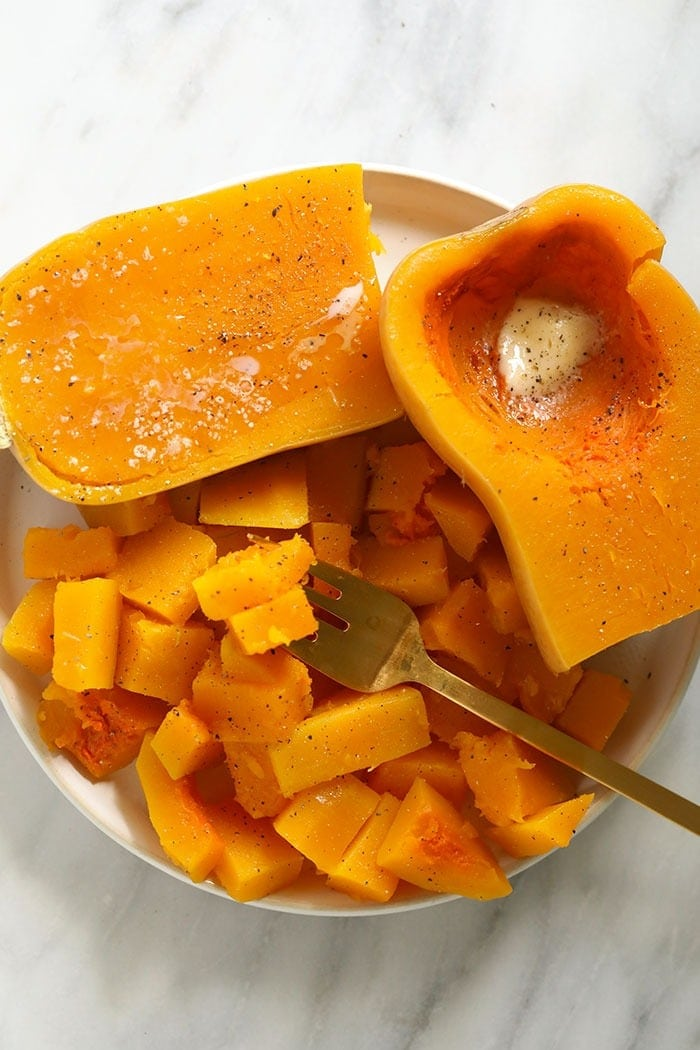 cooked butternut squash on a plate with butter, salt, and pepper