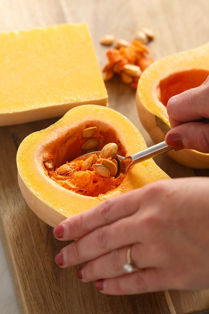 Scooping the innards out of butternut squash