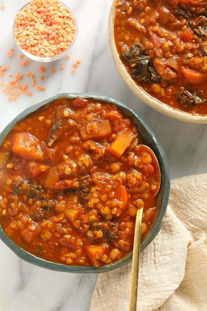 A bowl of lentil stew with a spoon in it.