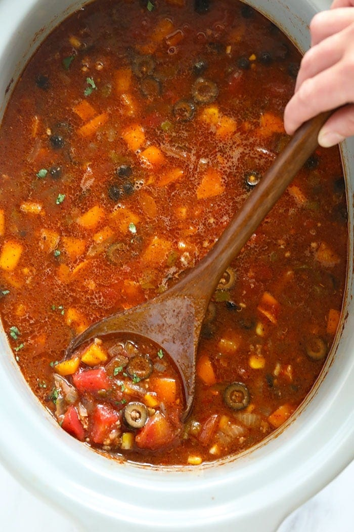 slow cooker taco soup being stirred with a spoon