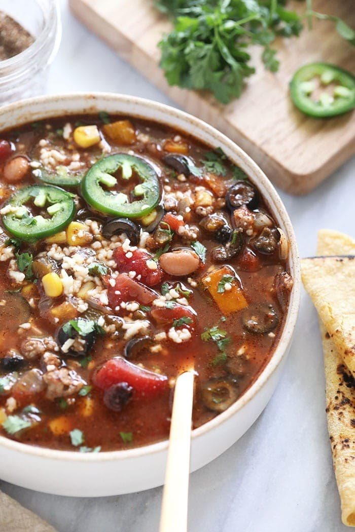 slow cooker taco soup in a bowl topped with cotija and jalapenos