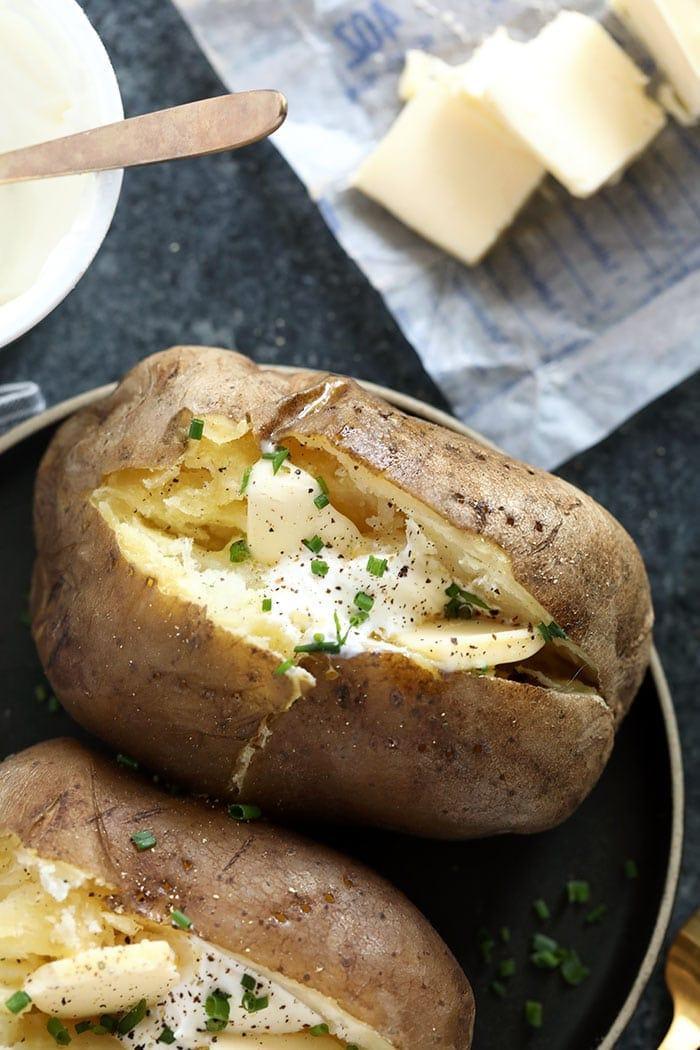 papas al horno con olla de barro cubiertas con cebollino y crema agria