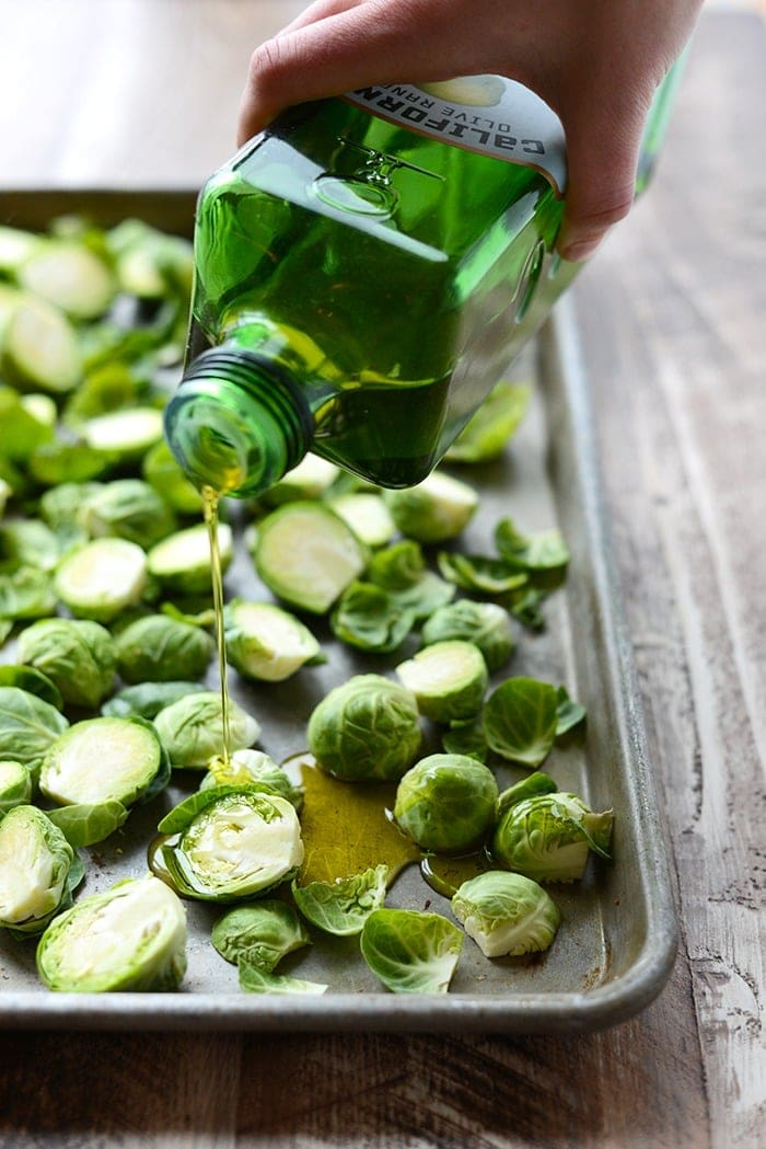 brussel sprouts being drizzled with olive oil