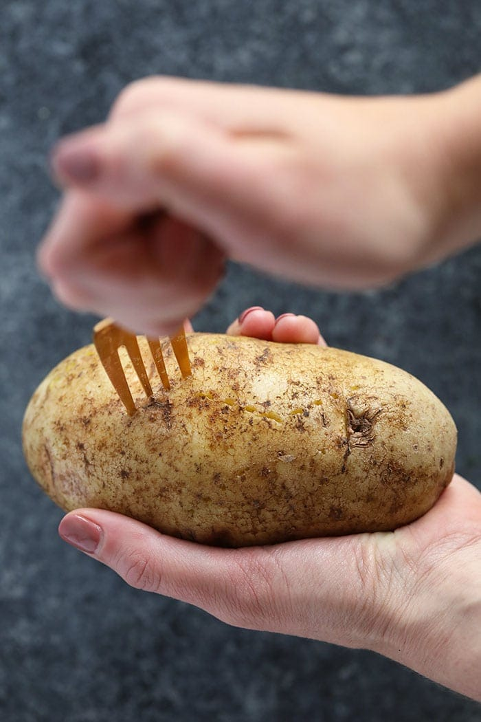 crock pot baked potato being speared with a fork