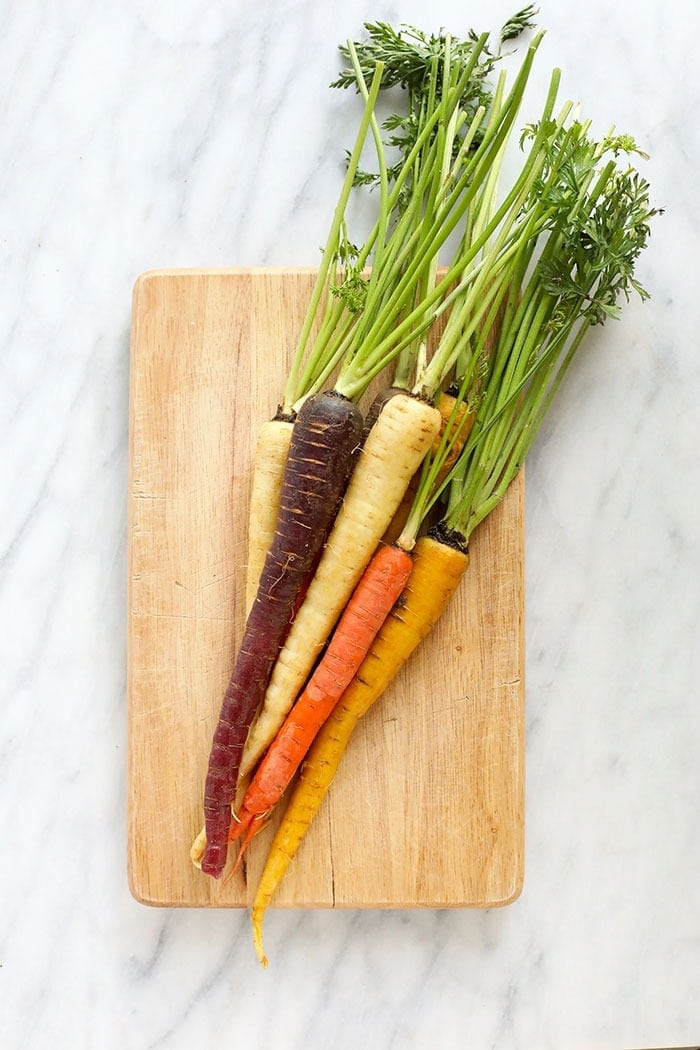 multi-colored carrots on a cutting board