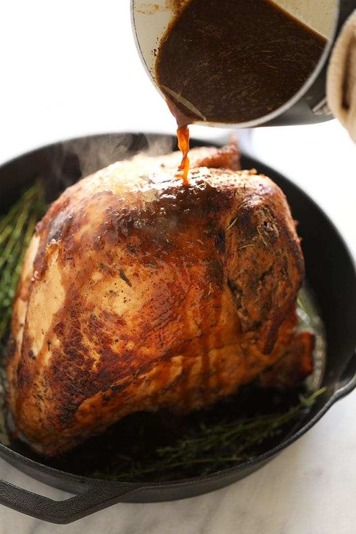 Pouring white wine sauce over the turkey