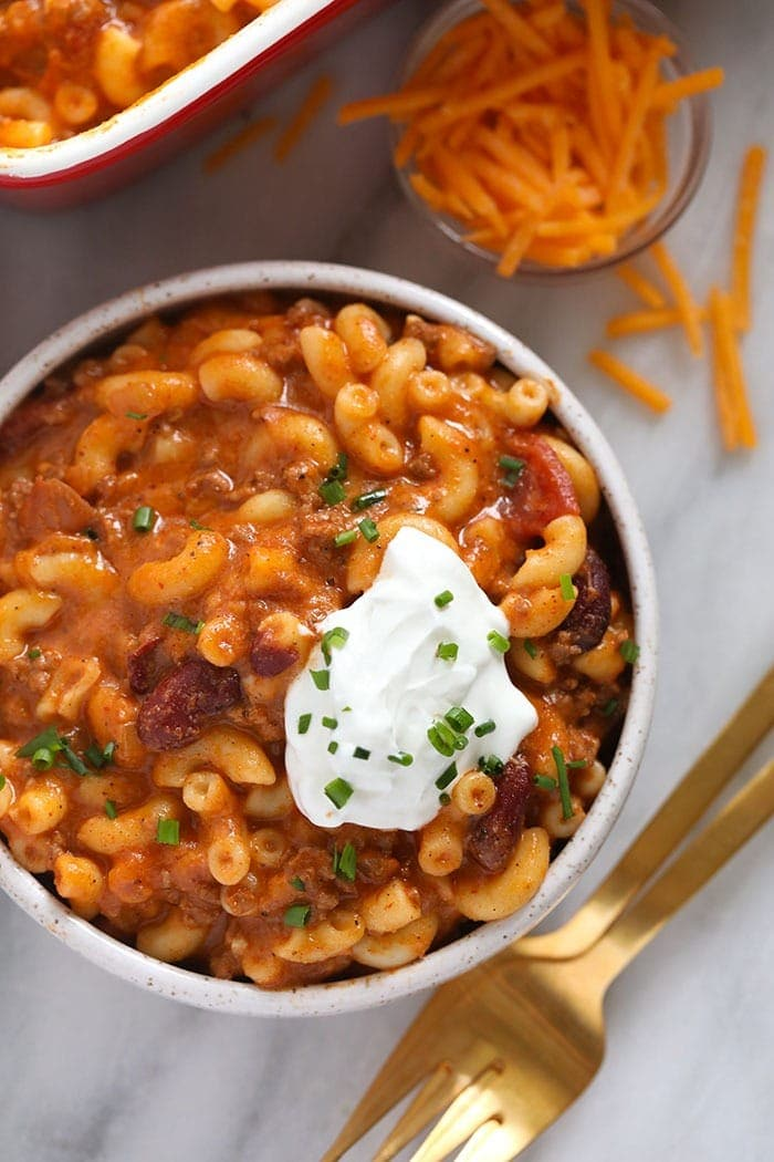 Chili mac in a bowl with greek yogurt scooped on top