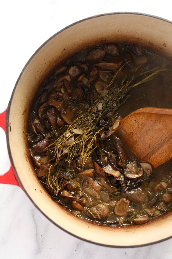 Mushroom gravy cooking down in a dutch oven