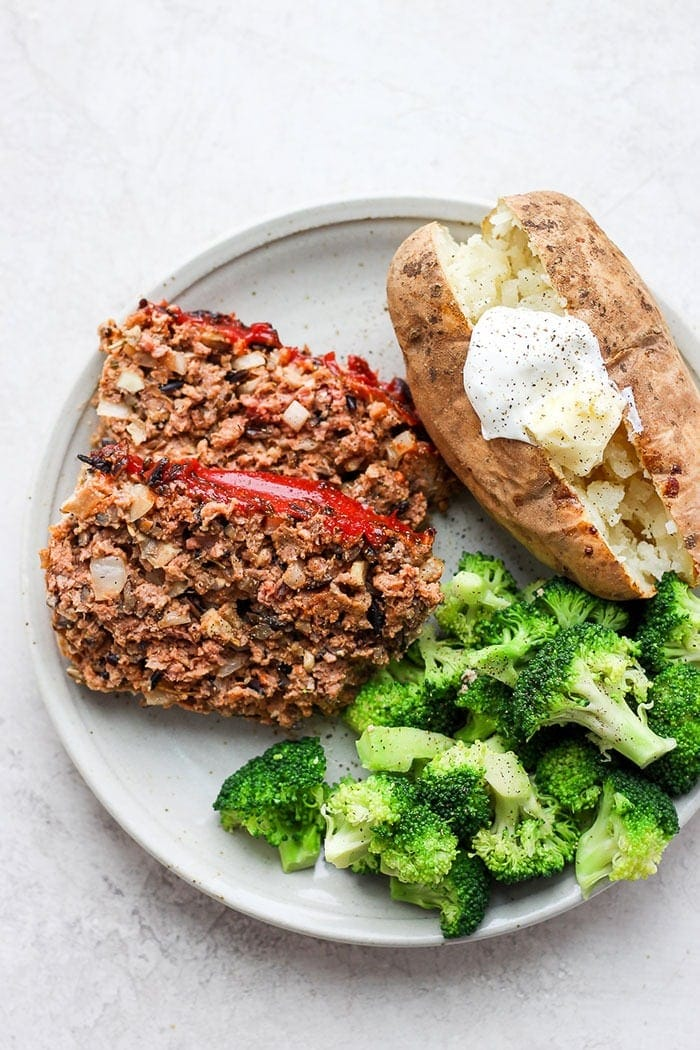 wild rice meatloaf on a plate with a baked potato and broccoli