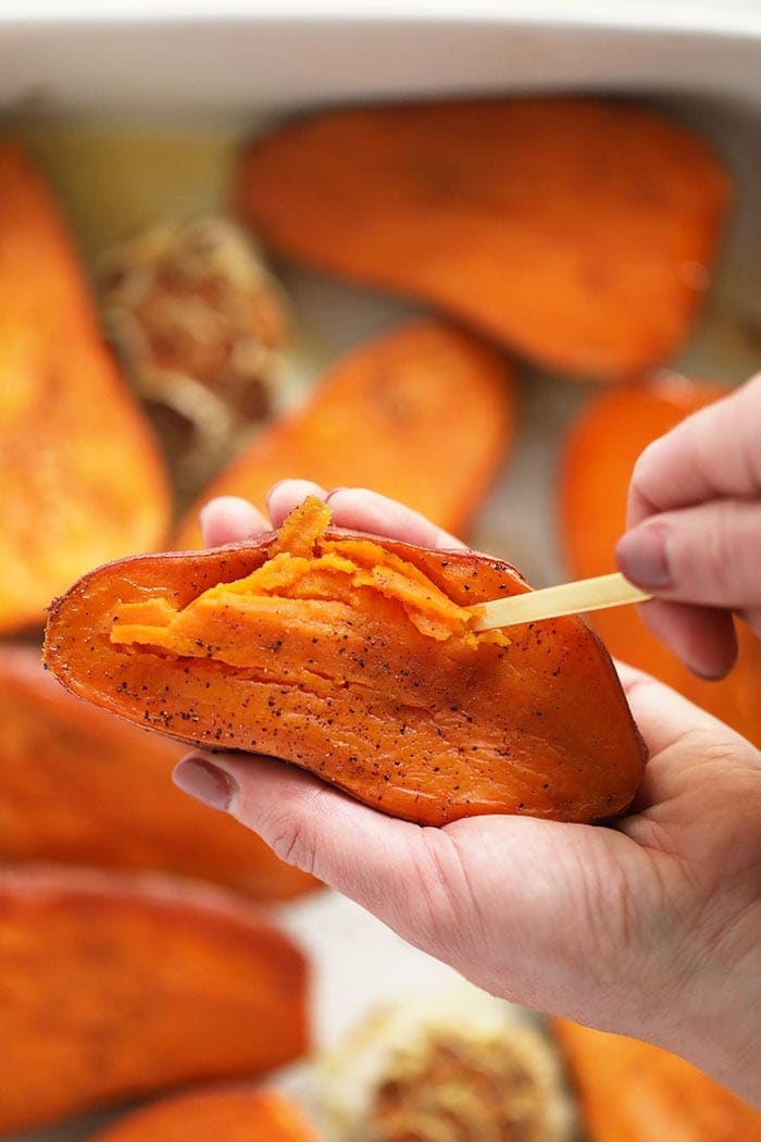 scooping out sweet potato flesh with spoon