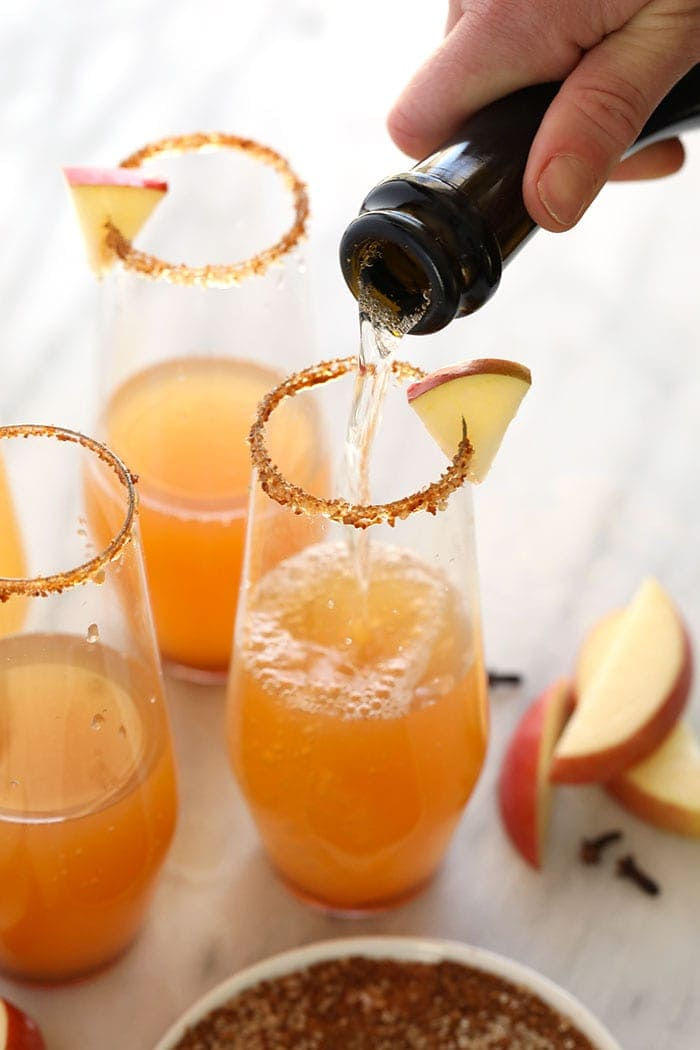 pouring champagne in a festive glass to make a apple cider champagne cocktail