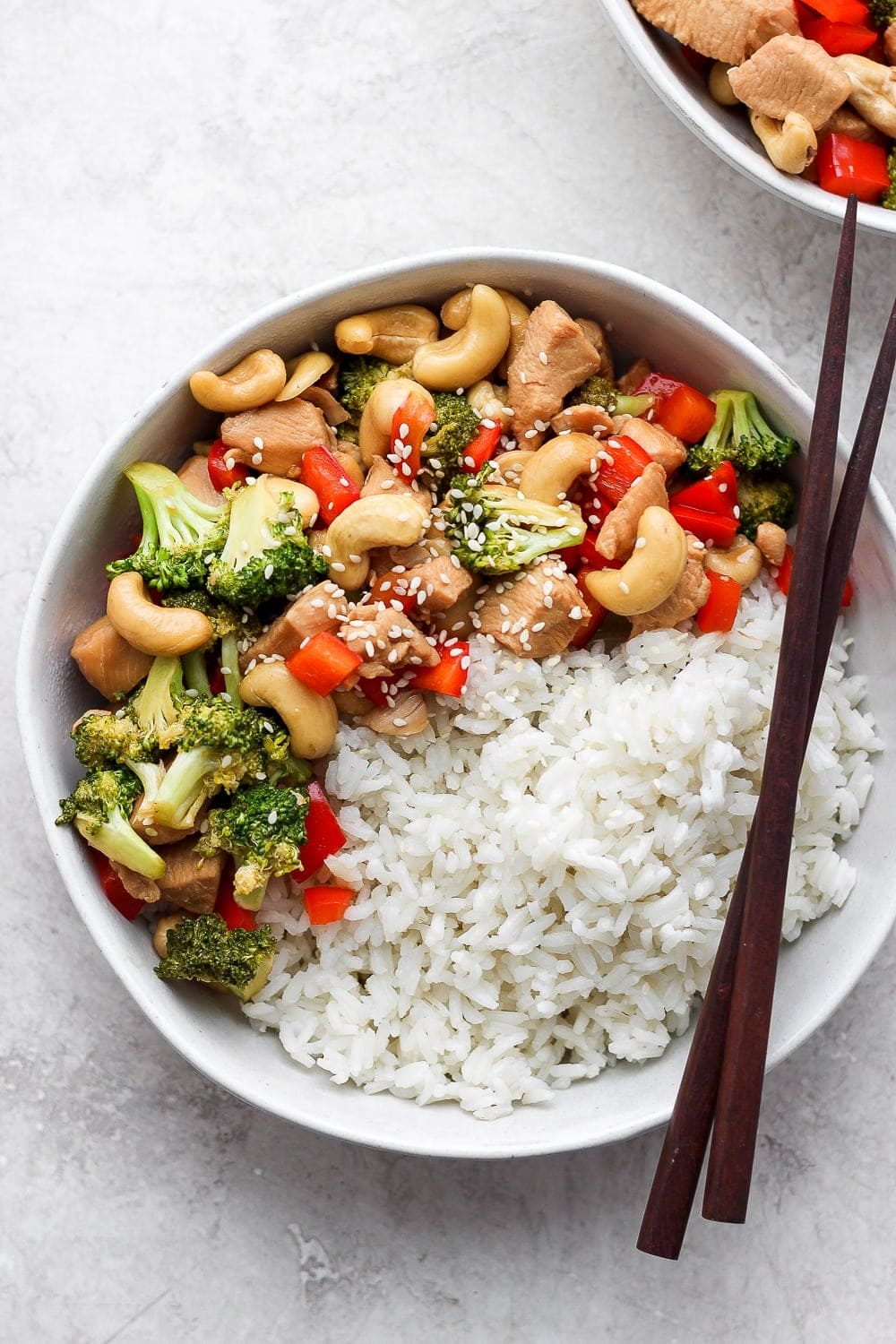 instant pot cashew chicken in a bowl with rice and chopsticks