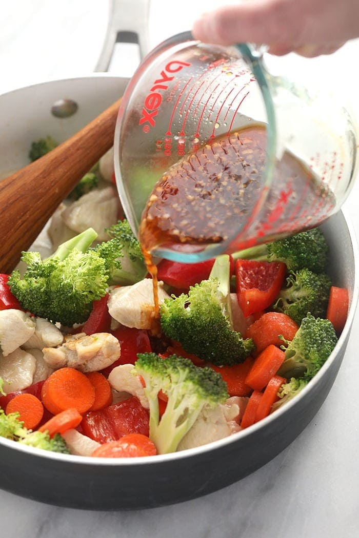 Pouring teriyaki sauce over chicken and vegetables