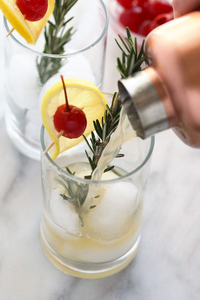 pouring a rosemary collins in a glass