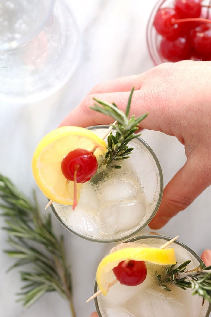 rosemary collins in a glass garnished with a sprig of rosemary