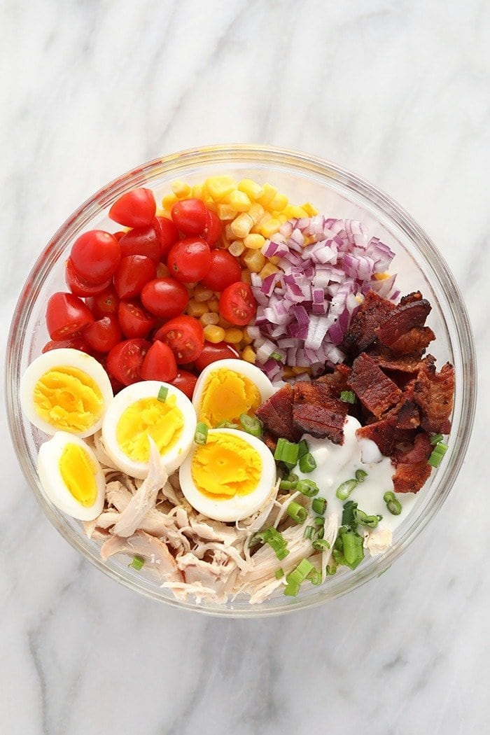 rotisserie chicken cobb salad ingredients in a bowl ready to be mixed