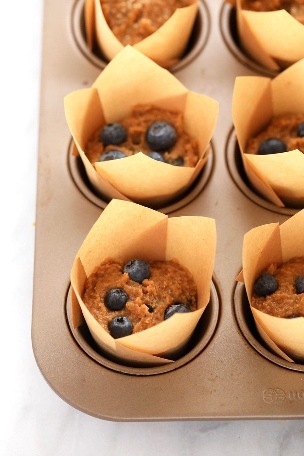 almond flour blueberry muffins in muffin liners ready to be baked