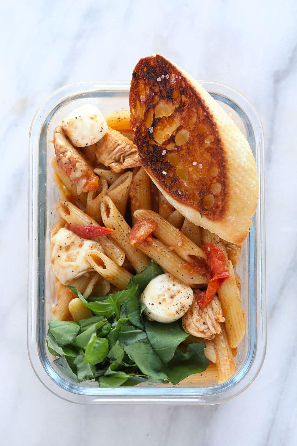 Caprese Chicken Pasta in a meal prep container