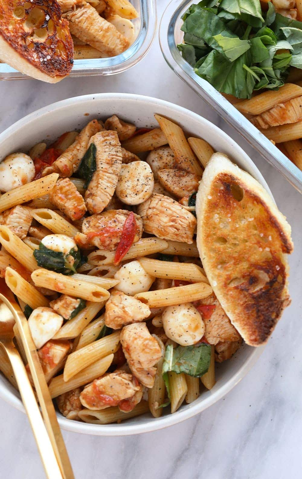 healthy caprese chicken pasta in a bowl served with a slice of french bread
