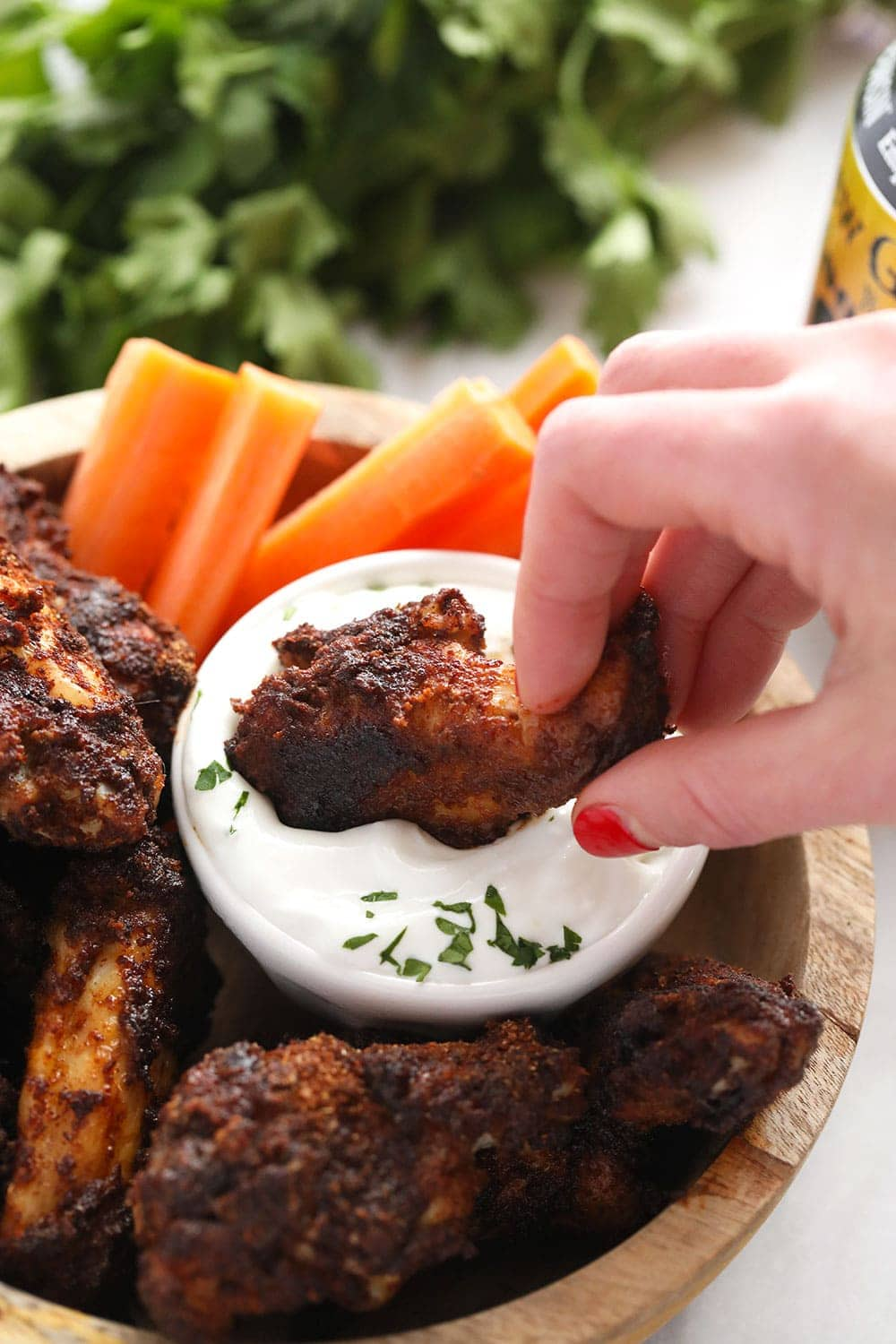 Dipping a chicken wing into blue cheese dressing