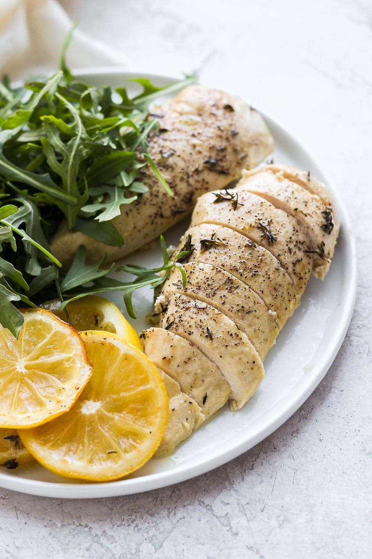 Sliced baked lemon chicken on plate.