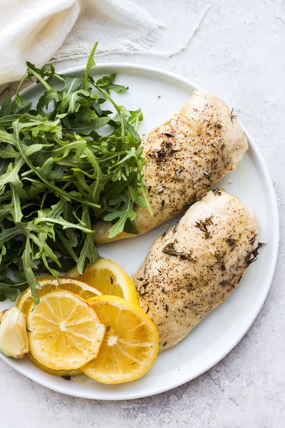 Baked lemon chicken breast on a plate.