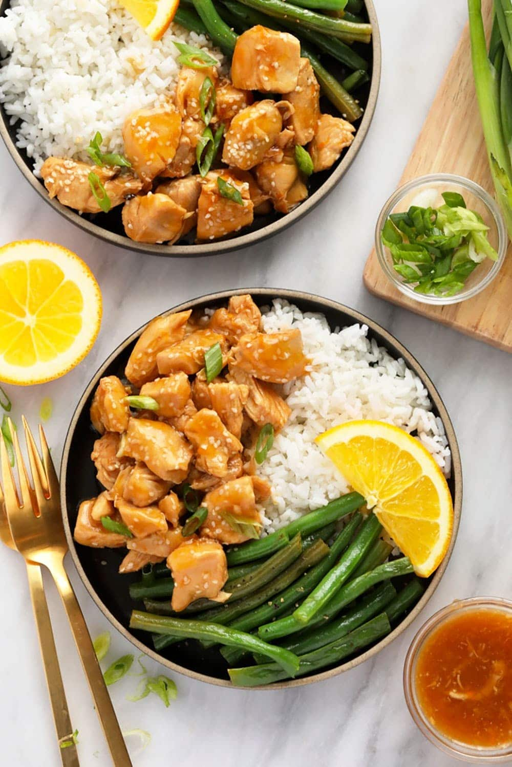 orange chicken on a plate with rice and beans