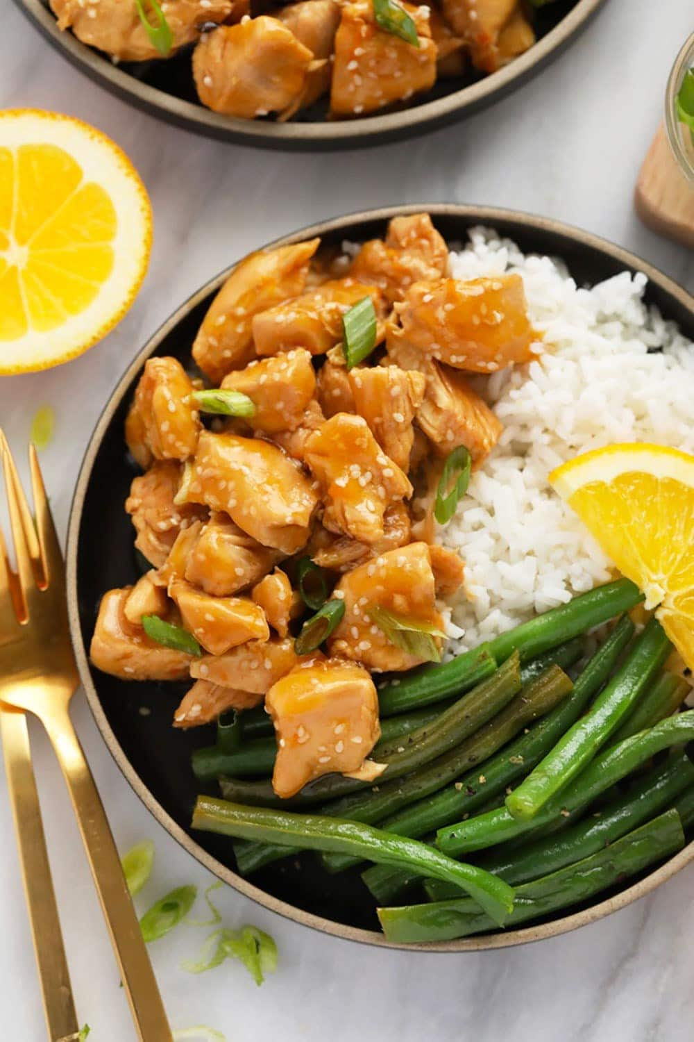 Orange chicken, white rice, and green beans on a plate