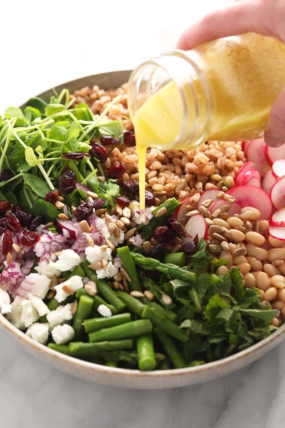 homemade lemon vinaigrette dressing being poured over a salad