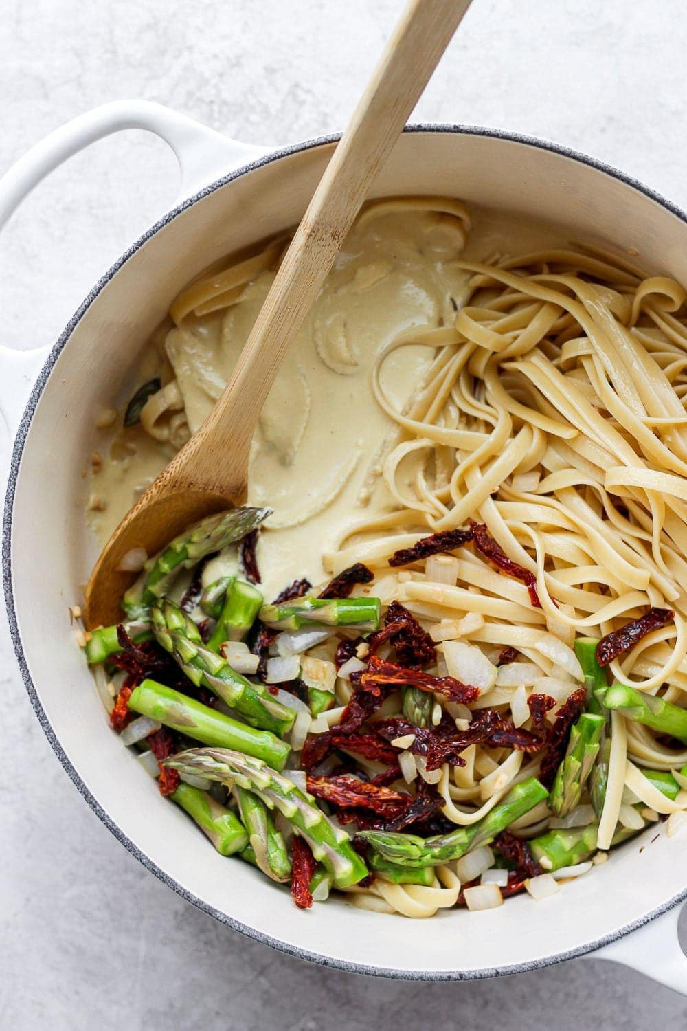 creamy vegan asparagus pasta in a dutch oven ready to be tossed together with veggies and creamy sauce