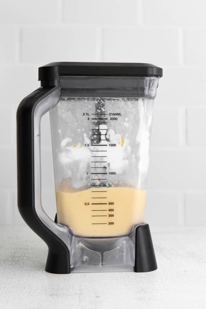Creamy mango smoothie in a blender.