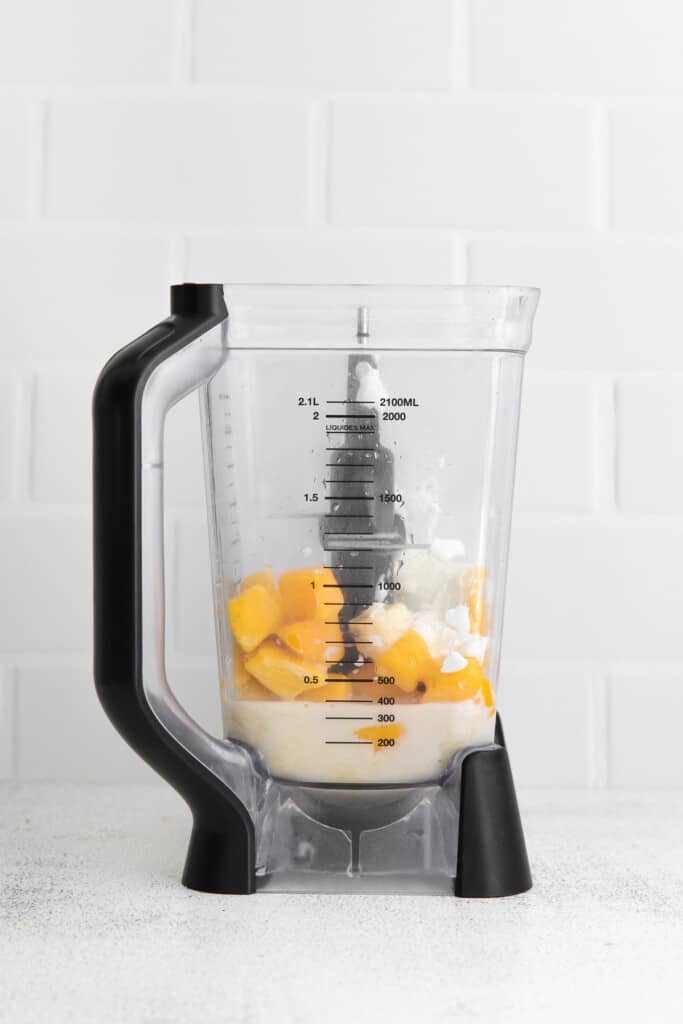 Frozen mango and other ingredients in a high speed blender.