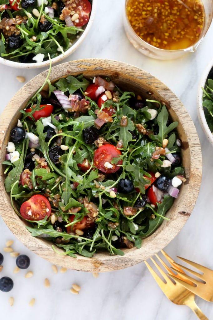 Arugula Salad in a mixing bowl.
