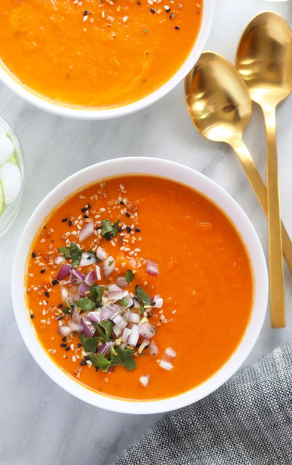 instant pot sweet potato carrot ginger soup in a bowl topped with diced onion
