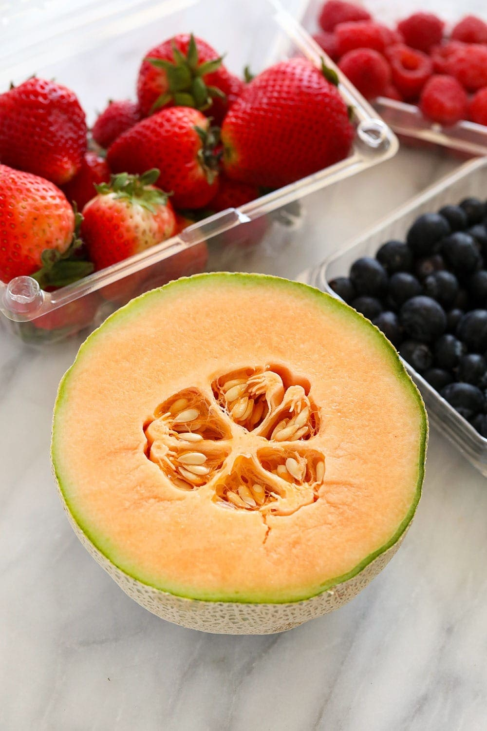 cantaloupe, strawberries and blueberries ready to be used in a fruit salad
