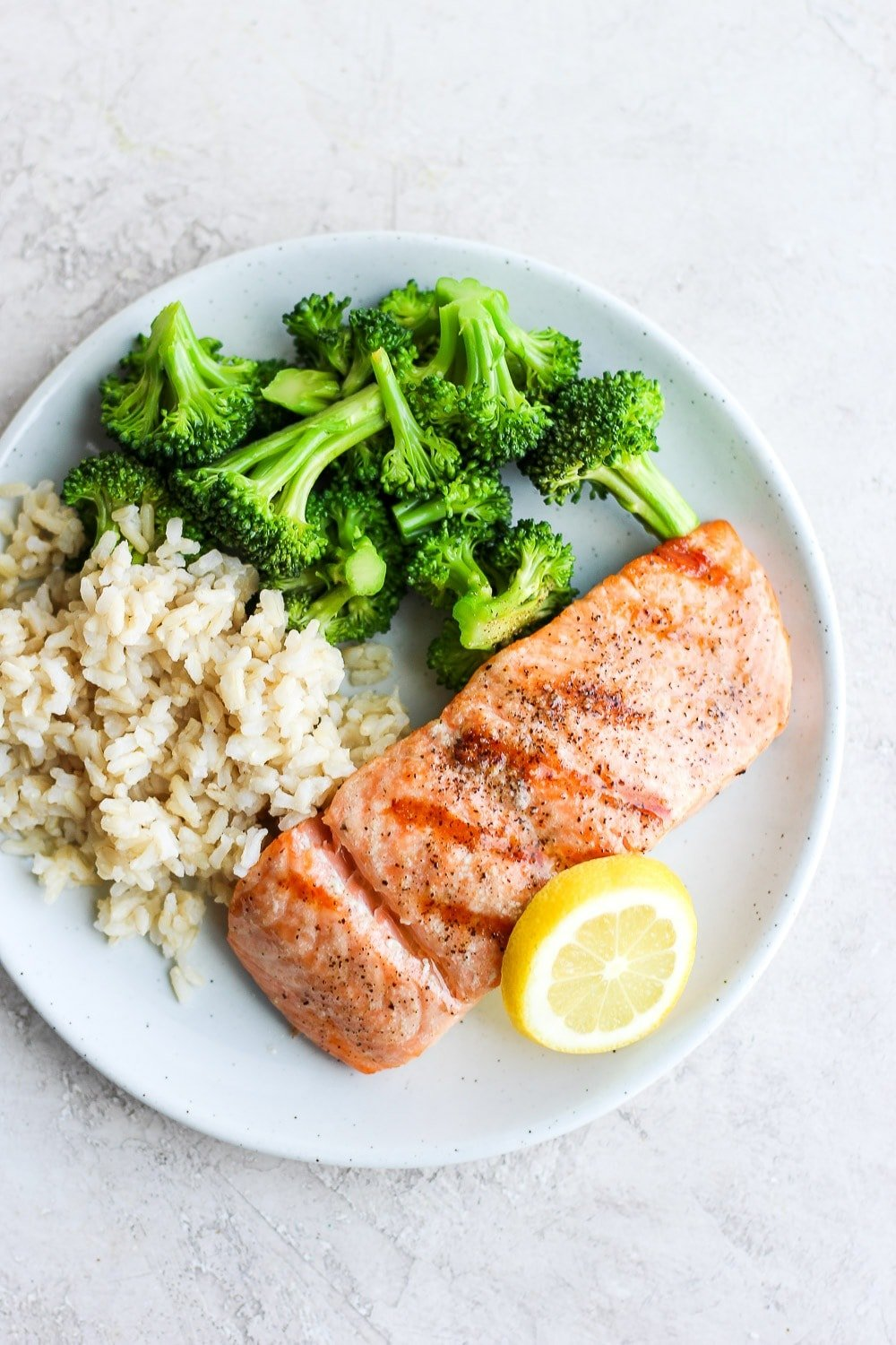 grilled salmon on a plate with broccoli and rice