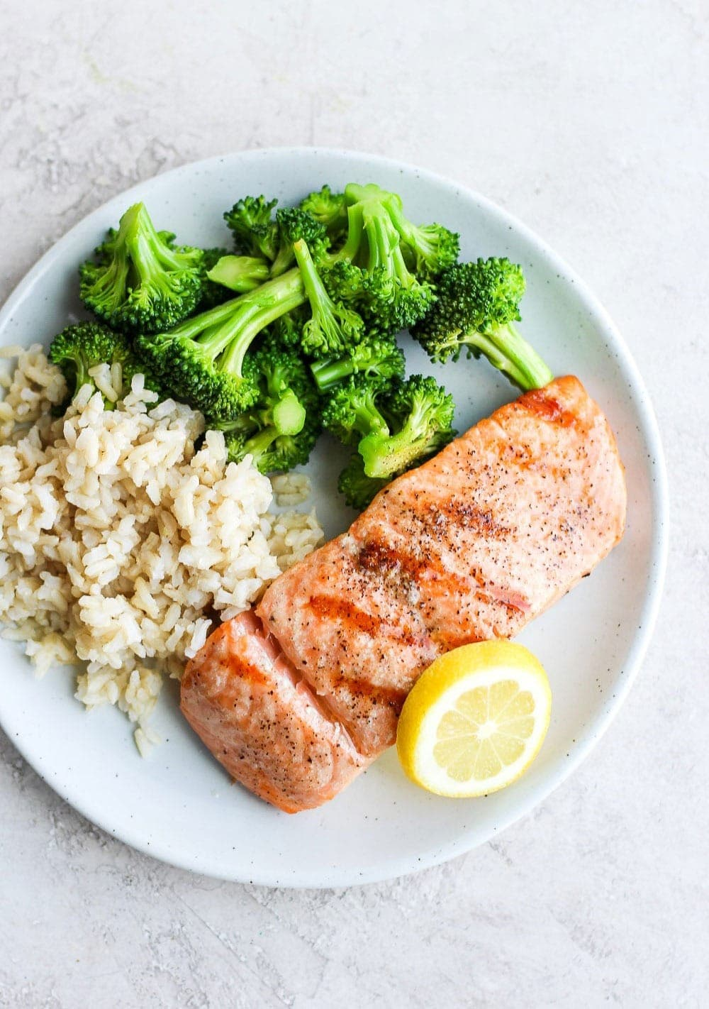 grilled salmon on a plate with a slice of lemon