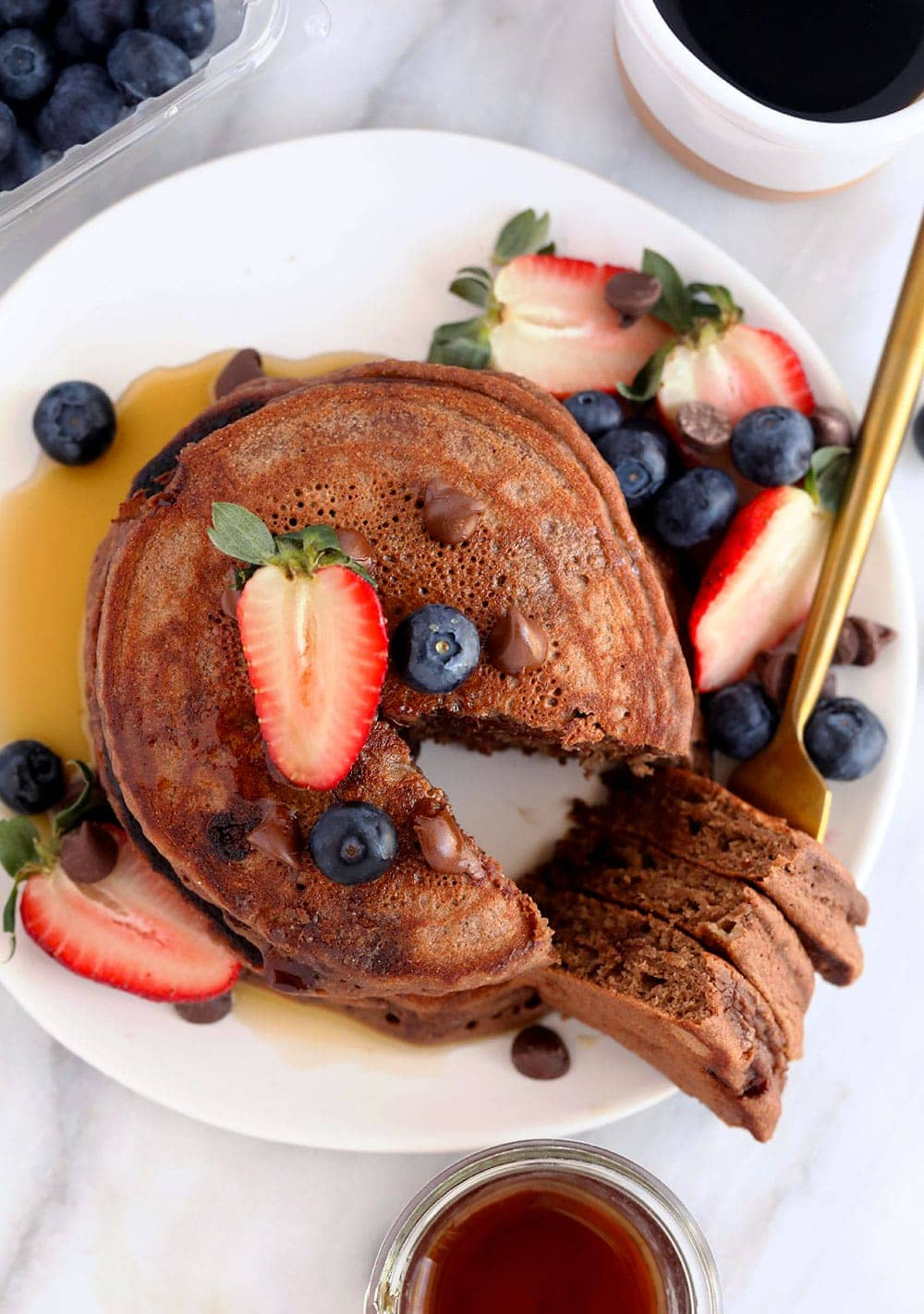 chocolate chocolate chip pancakes on a plate topped with blueberries and strawberries
