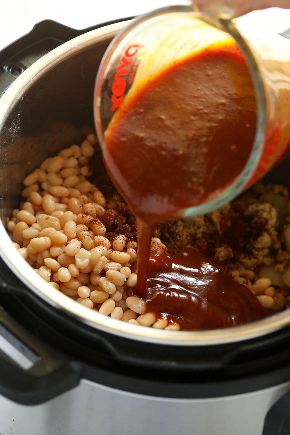 Pouring BBQ sauce into the Instant Pot!