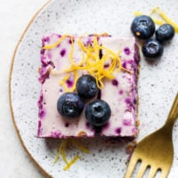 blueberry cheesecake bar on a plate topped with fresh berries